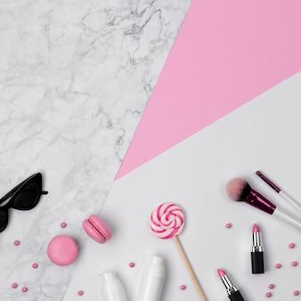 Vista dall'alto del banco di bellezza della donna con accessori, cosmetici decorativi e dolci sul tavolo pastello rosa, marmo e bianco.