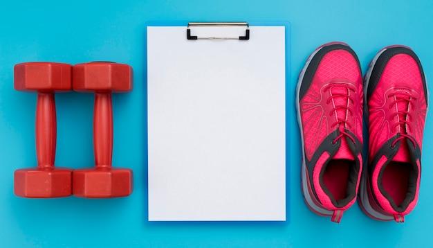 Vista dall'alto del blocco note con pesi e scarpe da ginnastica