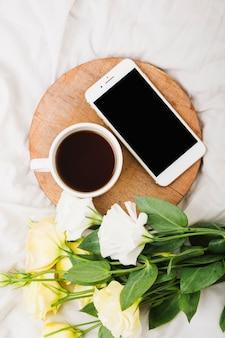 Vista dall'alto del bouquet di fiori con tazza di caffè e telefono cellulare sul letto