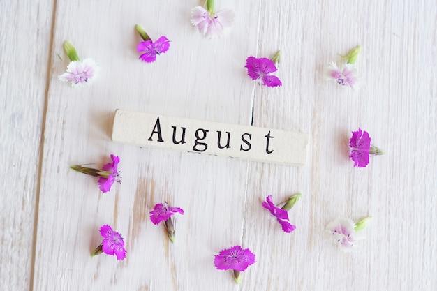 Vista dall'alto del calendario in legno con sighn di luglio e fiori rosa.