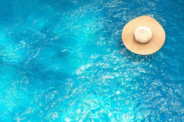 Vista dall'alto del cappello di paglia che galleggia sulla piscina con sfondo estivo.
