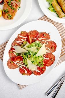 Vista dall'alto del carpaccio di manzo con rucola di parmigiano e pomodori