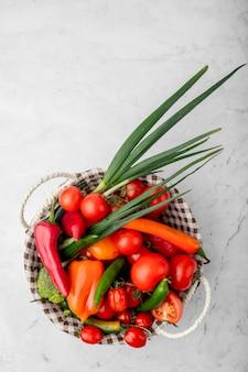 Vista dall'alto del cesto pieno di verdure sulla superficie bianca