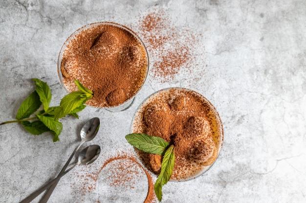 Vista dall'alto del classico dessert tiramisù con cacao e biscotti savoyardi in vetro decorato mirtilli e menta su grigio