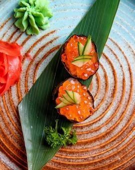 Vista dall'alto del classico sushi giapponese con caviale rosso su foglia di bambù servito con salsa allo zenzero e wasabi su un piatto