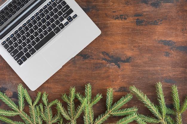 Vista dall'alto del computer portatile, natale in legno con rami di abete, piatto disteso.