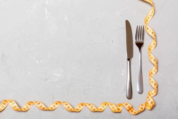Vista dall'alto del concetto di obesità con forchetta, coltello e nastro di misurazione arricciato su sfondo di cemento con spazio per le vostre idee creative