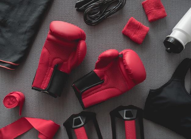 Vista dall'alto del concetto di palestra di boxe con guantoni da boxe, attrezzatura da palestra, corda per saltare e accessori su sfondo stuoia di yoga.