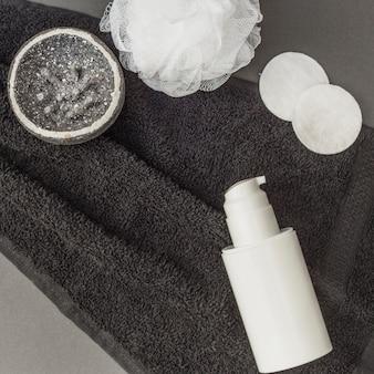 Vista dall'alto del corpo scrub; spugna; luffa; bottiglia e asciugamano cosmetici
