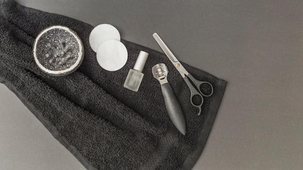Vista dall'alto del corpo scrub; spugna; smalto per unghie; forbici e dispositivo di rimozione del callo sul telo
