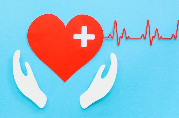 Vista dall'alto del cuore di carta con battito cardiaco e mani