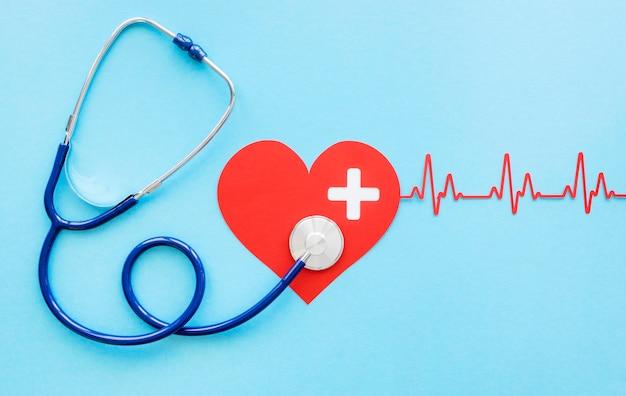 Vista dall'alto del cuore di carta con battito cardiaco e stetoscopio per il giorno del cuore