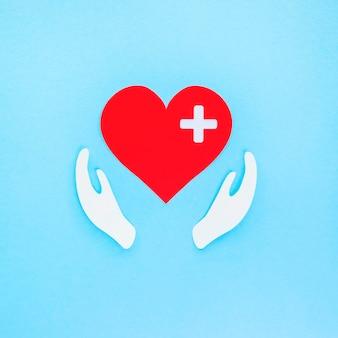 Vista dall'alto del cuore di carta e delle mani per il giorno del cuore