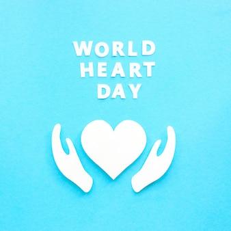 Vista dall'alto del cuore di carta e delle mani per la giornata mondiale del cuore