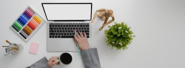 Vista dall'alto del designer che lavora su laptop mock-up, forniture di design e bere caffè
