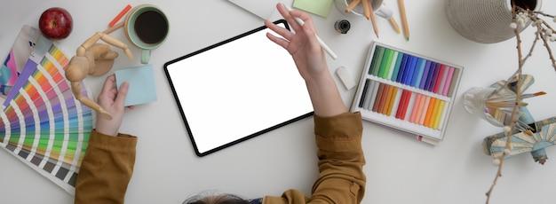 Vista dall'alto del designer femminile che lavora in uno spazio di lavoro minimo con tablet mock-up, forniture di design e tazza di caffè