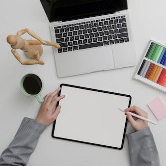 Vista dall'alto del designer femminile che sveglia con dispositivi digitali e forniture di design
