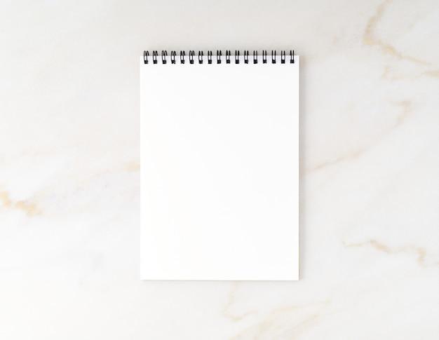 Vista dall'alto del desktop in marmo beige con blocco note. mock up, spazio vuoto