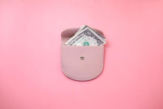 Vista dall'alto del dollaro statunitense in un portafoglio su sfondo rosa.