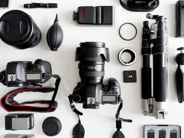 Vista dall'alto del fotografo dello spazio di lavoro con fotocamera digitale, flash, kit di pulizia, memory card, treppiede e accessorio per fotocamera