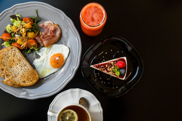 Vista dall'alto del frullato; cheesecake; tè; crostini; insalata; bacon; uovo fritto e pane tostato sul piatto grigio su sfondo nero
