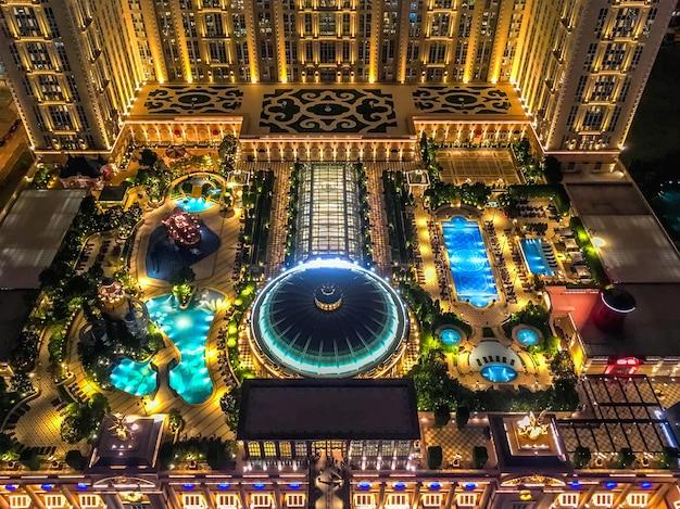Vista dall'alto del giardino pensile dell'hotel parigino a macao. illuminazione notturna della piscina.