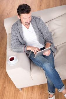 Vista dall'alto del giovane sdraiato sul divano nel suo appartamento