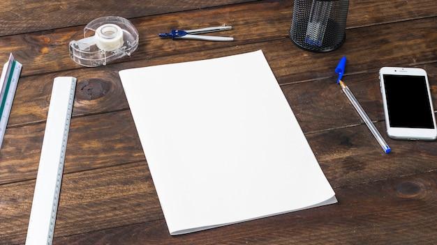 Vista dall'alto del libro bianco con cartolerie e cellulare sul tavolo di legno