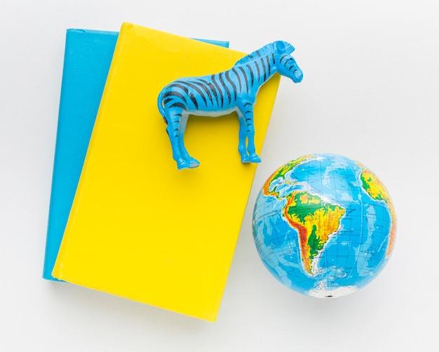 Vista dall'alto del libro con la statuetta di zebra e il pianeta terra per la giornata degli animali