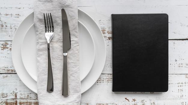 Vista dall'alto del libro di menu con piatti e posate