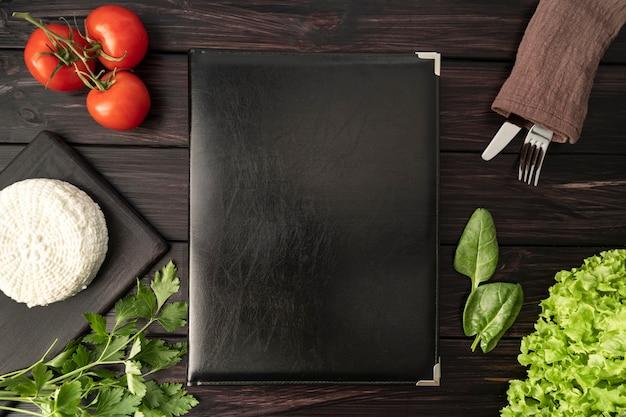 Vista dall'alto del libro menu vuoto con pomodori e posate