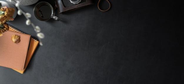 Vista dall'alto del luogo di lavoro alla moda scuro con spazio di copia e forniture per ufficio sulla scrivania in pelle nera