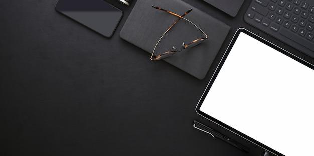 Vista dall'alto del luogo di lavoro alla moda scuro con tablet schermo vuoto