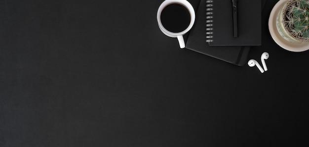 Vista dall'alto del luogo di lavoro alla moda scuro con tazza di caffè e articoli per ufficio sul tavolo nero