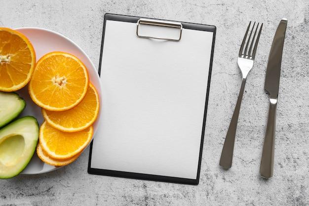 Vista dall'alto del menu vuoto con fetta d'arancia e avocado