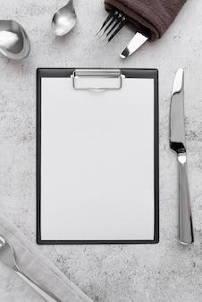 Vista dall'alto del menu vuoto con forchette e coltelli