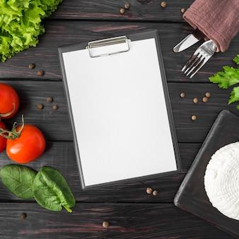 Vista dall'alto del menu vuoto con pomodori e spinaci