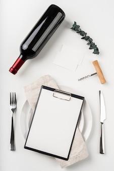 Vista dall'alto del menu vuoto con vino e cavatappi
