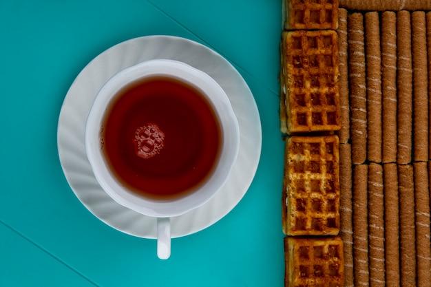 Vista dall'alto del modello di bastoncini e torte croccanti con una tazza di tè su sfondo blu