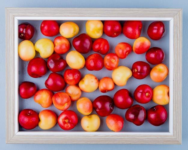 Vista dall'alto del modello di ciliegie nel telaio sulla superficie blu