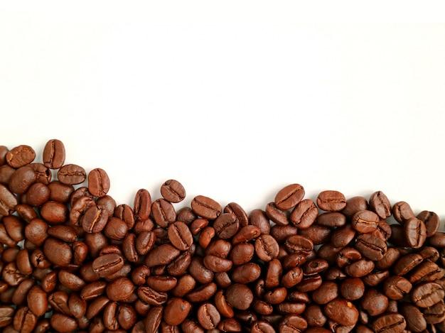 Vista dall'alto del mucchio di chicchi di caffè tostato su bianco
