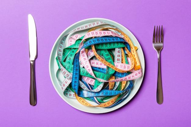 Vista dall'alto del mucchio di nastri di misurazione colorate nel piatto su sfondo viola