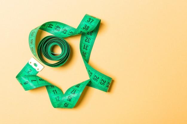 Vista dall'alto del nastro di misura ridotta in una spirale con spazio di copia. di accessori per cucire o dieta sana sull'arancia
