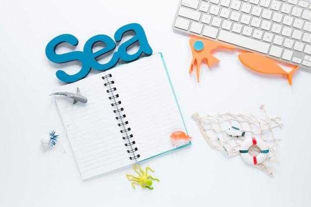 Vista dall'alto del notebook con rete da pesca e figurine di pesce