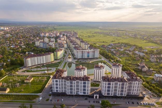 Vista dall'alto del paesaggio urbano in via di sviluppo urbano con alti edifici di appartamenti e case di periferia.