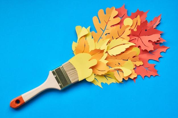 Vista dall'alto del pennello caricato con foglie di autunno su carta blu