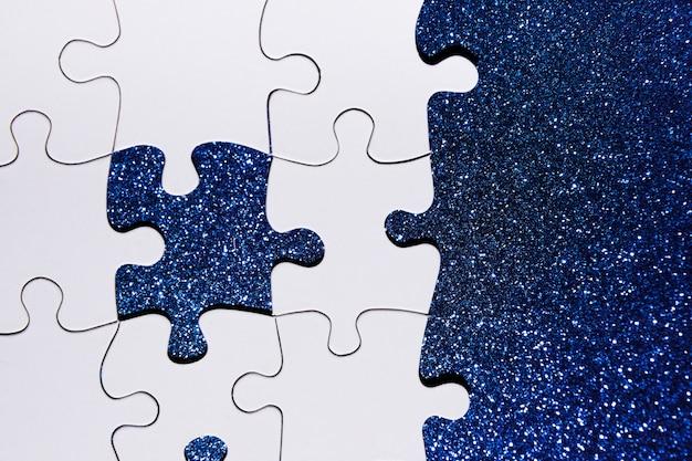 Vista dall'alto del pezzo di puzzle su sfondo blu glitter