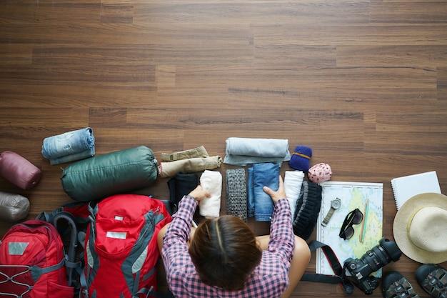 Vista dall'alto del piano della donna del viaggiatore e pianificazione dello zaino