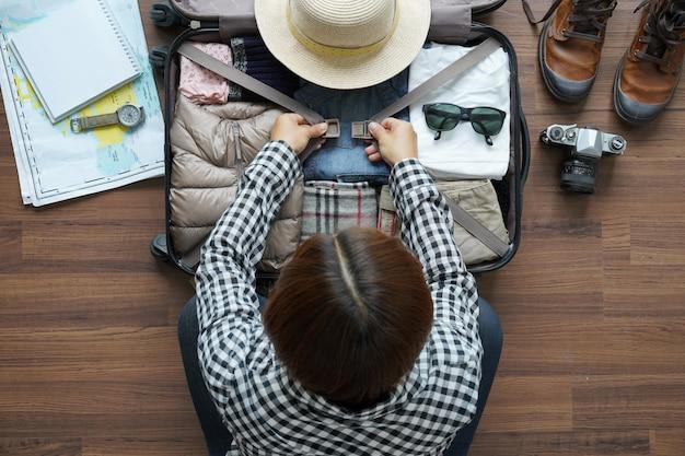 Vista dall'alto del piano di donna viaggiatore e lo zaino pianificazione viaggio di vacanza
