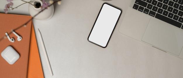Vista dall'alto del piano di lavoro con smartphone, laptop, cancelleria, accessori, decorazioni e spazio di copia del percorso di residuo della potatura meccanica